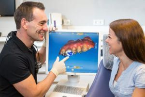Dentist showing patient teeth view on camera